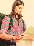 Man tourist backpacker reading map. Summer travel. Stock Image