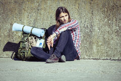 Man tourist backpacker sitting by grunge wall outdoor Royalty Free Stock Photography