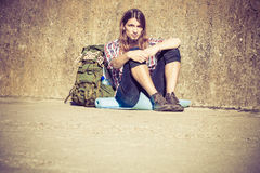 Man tourist backpacker sitting by grunge wall outdoor Royalty Free Stock Photo