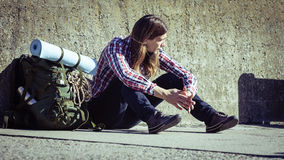 Man tourist backpacker sitting by grunge wall outdoor Stock Image