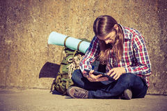 Man tourist backpacker sitting with tablet outdoor Royalty Free Stock Images