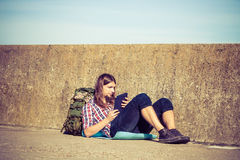 Man tourist backpacker sitting with tablet outdoor Royalty Free Stock Photography