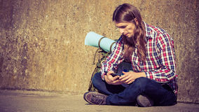 Man tourist backpacker sitting with tablet outdoor Stock Photos