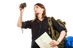 Man tourist backpacker taking photo with camera. Man tourist backpacker on trip taking photo picture with camera. Young guy hiker backpacking holding map Royalty Free Stock Image