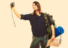 Man tourist backpacker taking photo with camera. Man tourist backpacker on trip taking photo picture with camera. Young guy hiker backpacking holding map Stock Photography