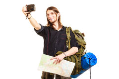 Man tourist backpacker taking photo with camera. Man tourist backpacker on trip taking photo picture with camera. Young guy hiker backpacking holding map Stock Image