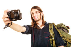 Man tourist backpacker taking photo with camera. Man tourist backpacker on trip taking photo picture with camera. Young guy hiker backpacking. Summer vacation Stock Photography