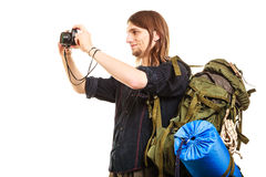Man tourist backpacker taking photo with camera. Man tourist backpacker on trip taking photo picture with camera. Young guy hiker backpacking. Summer vacation Royalty Free Stock Images