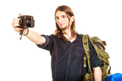 Man tourist backpacker taking photo with camera. Man tourist backpacker on trip taking photo picture with camera. Young guy hiker backpacking. Summer vacation Stock Images