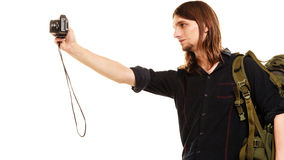 Man tourist backpacker taking photo with camera. Man tourist backpacker on trip taking photo picture with camera. Young guy hiker backpacking. Summer vacation Stock Photos
