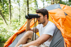 Man tourist with binoculars sitting near touristic tent in forest Stock Photo