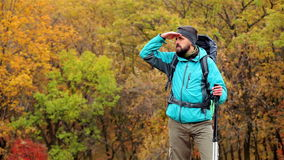 Man tourist in a blue jacket with a backpack looks around stock footage