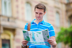 Man tourist with a city map and backpack in Europe. Caucasian boy looking at the map of European city in search of Royalty Free Stock Photos
