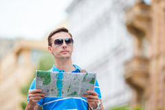 Man tourist with a city map and backpack in Europe. Caucasian boy looking at the map of European city in search of Royalty Free Stock Image