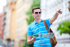 Man tourist with a city map and backpack in Europe. Caucasian boy looking at the map of European city in search of Royalty Free Stock Images