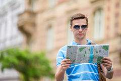 Man tourist with a city map and backpack in Europe street. Caucasian boy looking with map of European city. Happy young man with a city map and a backpack Royalty Free Stock Photo