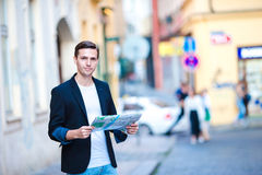 Man tourist with a city map and backpack in Europe street. Caucasian boy looking with map of European city. Happy young man with a city map and a backpack Stock Photo