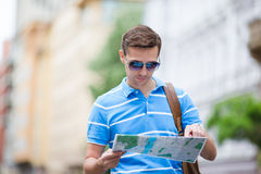 Man tourist with a city map and backpack in Europe street. Caucasian boy looking with map of European city. Royalty Free Stock Image