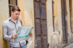 Man tourist with a city map and backpack in Europe street. Caucasian boy looking with map of European city in search of Stock Image