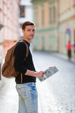 Man tourist with a city map and backpack in Europe street. Caucasian boy looking with map of European city in search of Royalty Free Stock Photo
