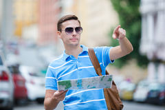 Man tourist with a city map and backpack in Europe street. European vacation. Happy young man with a city map and a backpack smiling Stock Image