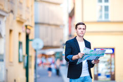 Man tourist with a city map in Europe. Young guy looking at the map of European city in search of attractions. Happy young man with a city map and a backpack Royalty Free Stock Photos