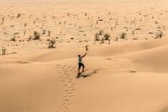 Man tourist in desert rub al khali Oman throwing sand Royalty Free Stock Photography