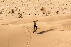 Man tourist in desert rub al khali Oman throwing sand 3 Stock Photo