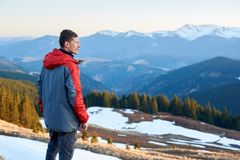 Male tourist enjoying beautiful panorama in the evening. Man tourist enjoying beautiful panorama in the evening on the blurred background snow-covered mountains Royalty Free Stock Images