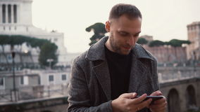Man tourist explores new city, takes selfie photos of city centre on the smartphone. Male enjoys trip to Rome, Italy. Stock Photos
