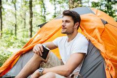 Man tourist with flask sitting at touristic tent in forest Royalty Free Stock Image