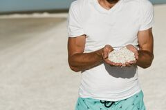 Free Man Tourist Holding Tiny White Sea Shells In Both Hands Stock Photography - 186428112