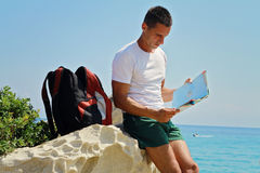 Man tourist looking at map infront of sea, active summer holiday vacation Royalty Free Stock Photo