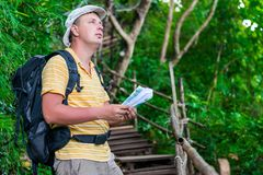 Man tourist lost, check with map and terrain. In the hike Stock Photos