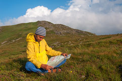 Man tourist in mountain read the map. Royalty Free Stock Images