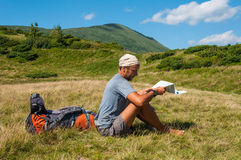 Man tourist in mountain read the map. Royalty Free Stock Image