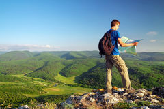 Man tourist in mountain read the map. Man on top of mountain. Tourism concept Stock Images