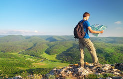 Man tourist in mountain read the map. Man on top of mountain. Stock Photo