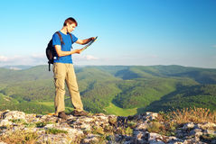Man tourist in mountain read the map. Man on top of mountain. Tourism concept Royalty Free Stock Photos