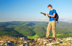Man tourist in mountain read the map. Man on top of mountain. Tourism concept Royalty Free Stock Photo