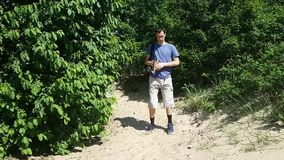 Man tourist out of the woods on the beach and unfolds the map. Terrain orientation. Hiking.  stock footage