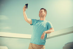 Man tourist on pier taking selfie with smartphone. Royalty Free Stock Images