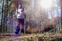 A man is a tourist in a pine forest with a backpack. A hiking tr. Ip through the forest. Pine reserve for tourist walks. A young man in a hike in the spring.r Royalty Free Stock Image