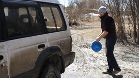 Man tourist pours SUV water from a bucket that would wash.  stock video footage