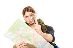Man tourist reading map with magnifying glass. Man tourist backpacker reading map with magnifying glass loupe. Young guy hiker searching looking for direction Stock Photography