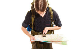 Man tourist reading map with magnifying glass. Man tourist backpacker reading map with magnifying glass loupe. Young guy hiker searching looking for direction Royalty Free Stock Images