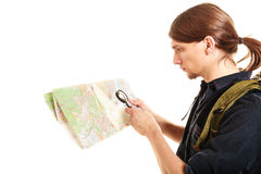 Man tourist reading map with magnifying glass. Man tourist backpacker reading map with magnifying glass loupe. Young guy hiker searching looking for direction Stock Images