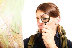 Man tourist reading map with magnifying glass. Man tourist backpacker reading map with magnifying glass loupe. Young guy hiker searching looking for direction Royalty Free Stock Photography