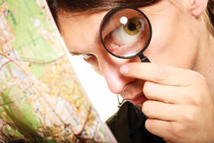 Man tourist reading map with magnifying glass. Man tourist backpacker reading map with magnifying glass loupe. Young guy hiker searching looking for direction Royalty Free Stock Image