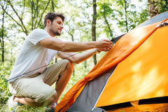 Man tourist setting up touristic tent in forest. Handsome young man tourist setting up touristic tent in forest Royalty Free Stock Image